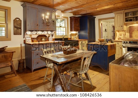 The kitchen in a primitive colonial style reproduction home, built with materials reclaimed from structures built in the late 1700's.  The room contains many antiques from the late 18th century. - stock photo