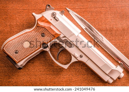 The knife and the pistol on the table. Top view, in red tone - stock photo