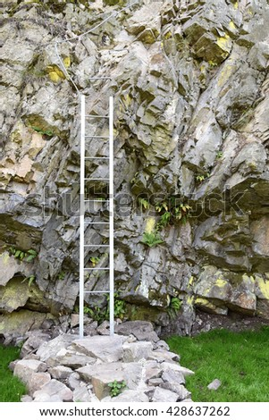 The ladder standing near rocks - stock photo