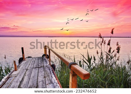 The lake is stained pink with dawn - stock photo