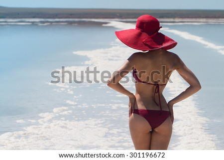 The lake with salt water. Sexy back of a beautiful woman in a red bikini