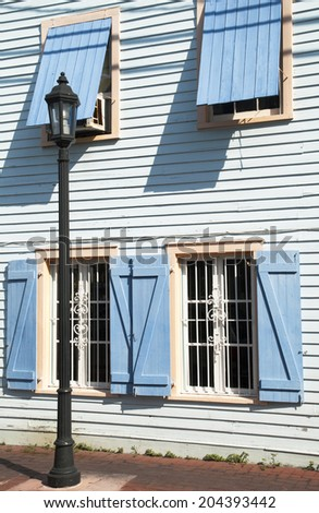 The lamppost standing by the wooden house painted in blue (Key West, Florida). - stock photo