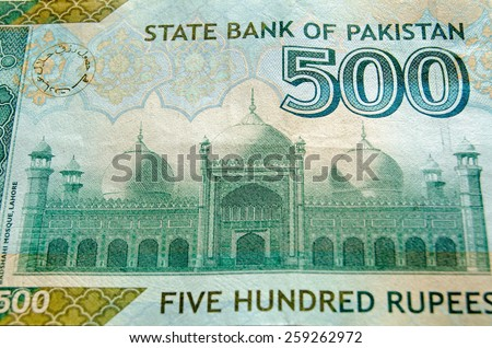 The landmark Badshahi Mosque in Lahore depicted on part of the 500 Rupee banknote of Pakistan. Used banknote, photographed at an angle with less than 80% of note showing. - stock photo