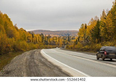 The landscape and the road. The colors of autumn. Low dark clouds.