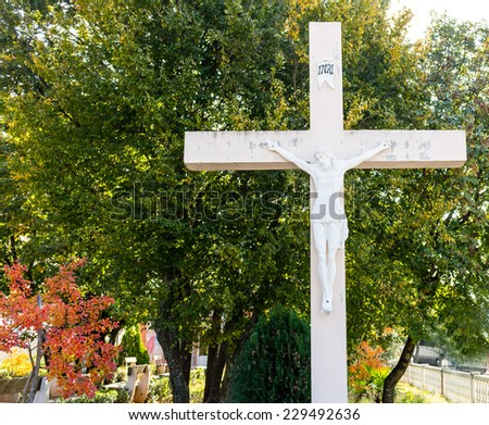 The large wooden White Cross with crucified Jesus Christ statue  at Apparition Mountain in Medugorje among green trees and weeds - stock photo