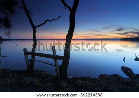 The last colours of sunset n at this peaceful secluded spot on St Georges Basin, near Jervis Bay, Australia.  A rustic timber  seat anchored between two trees allows one to sit reflect in peace.