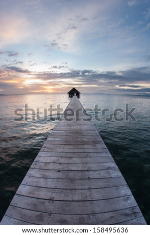 The last light of day falls on a long pier that stretches towards the horizon. This resort pier is on a remote tropical island in eastern Indonesia.