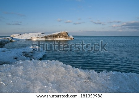 The last of the lake ice leaves the shoreline - stock photo