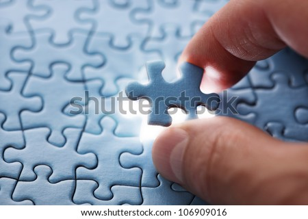 The last piece of jigsaw puzzle concept for solutions and completion - stock photo
