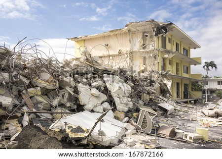 The last standing section of a hotel in the final stages of demolition with a large pile of jumbled concrete, steel rebar, and other debris in front waiting to be hauled away. - stock photo