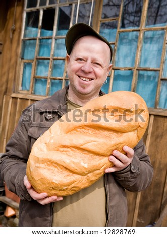 The laughing amusing man holds a huge loaf of bread near the rural house - stock photo