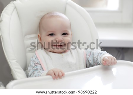 The laughing baby eating in a highchair at home - stock photo