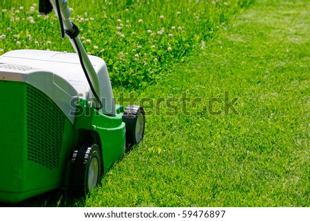 The Lawn mower in the yard on the grass - stock photo