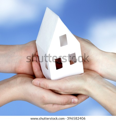 the layout of the house from a paper in human hands against the sky/peaceful sky and our house in our hands - stock photo
