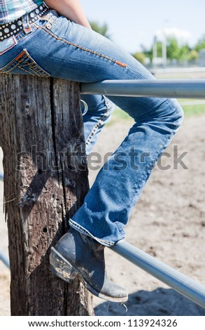 The leg of a young woman in blue jeans and dirty cowboy boots sitting on a fence. - stock photo