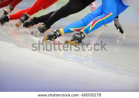 The legs of a group of ice-skaters on the ice. - stock photo