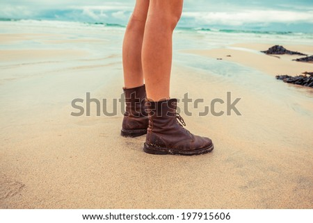The legs of a young woman as she is standing on the beach - stock photo
