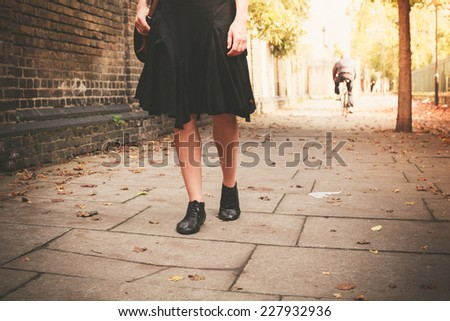 The legs of a young woman as she is walking in an alley on a sunny day