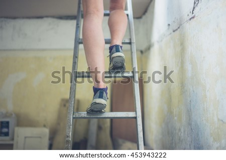 The legs of a young woman standing on a ladder to the loft - stock photo