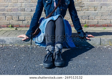The legs of a young woman wearing trendy clothes as she is sitting on the street
