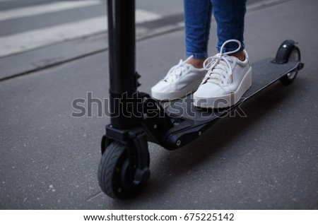 The legs of an unknown girl in white sneakers and tight jeans ride on a black electric scooter over a dark urban asphalt
