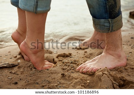The legs of men and women who are close to each other. Seashore. - stock photo