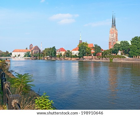 The leisure walk along the Oder River with a view on the spires of Wroclaw Cathedral on Tumski Island, Poland. - stock photo
