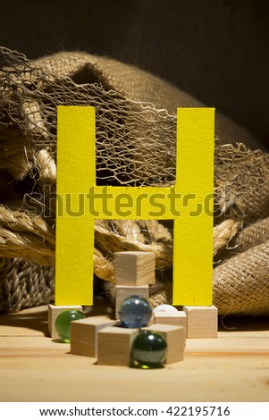 "The letter "" H "" by  Photo font "" Yellow Texture "" and subjects with active texture. Wood, burlap, glass beads. Preparation for graphic design"