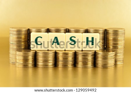 The letters  CASH with stacks of coins on gold background