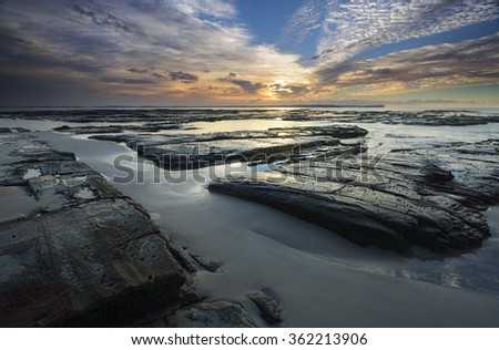 The light from the sun filtered through high cloud just after sunrise falls across the  rocks wet sand and shallow tidal flows at Plantation Point, Vincentia in Jervis Bay