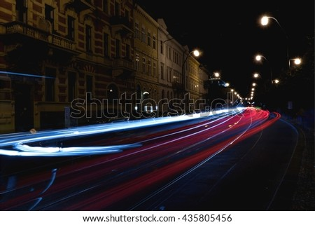 The light of car headlights in the night city - stock photo