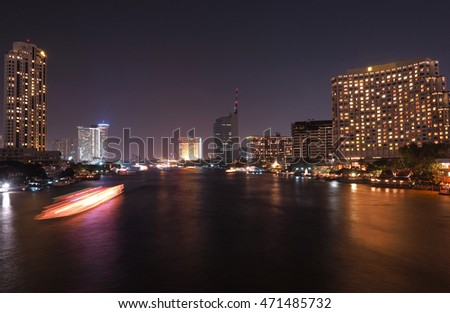 The light trails from boat on the river and modern building