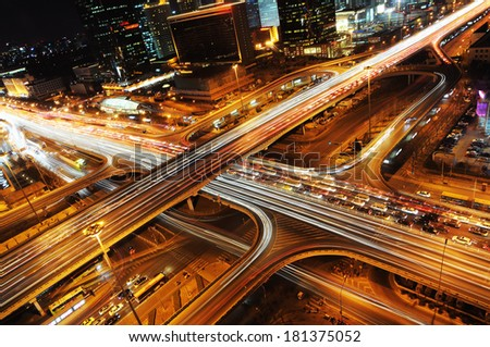 The light trails on the modern building background in Beijing china. - stock photo