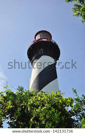 The lighthouse is set in a garden-like setting with trees all around the tower. - stock photo