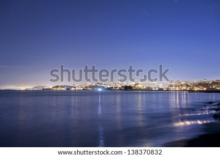 The lights of San Francisco Sparkle beyond the bay at twilight - stock photo