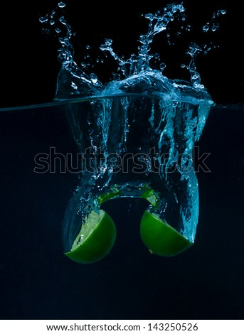 The lime slices falling into the water . - stock photo