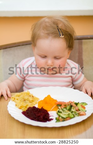 The litle child eats a vegetable salad