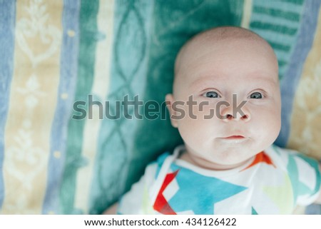 The little baby lies on the bed - stock photo