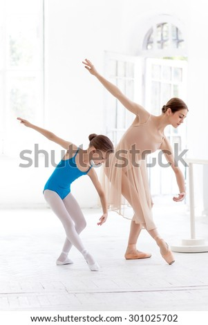 The little ballerina in tutu with personal classic ballet teacher posing together on a white dance studio background - stock photo