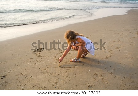 The little beautiful girl the blonde draws on sand on seacoast - stock photo