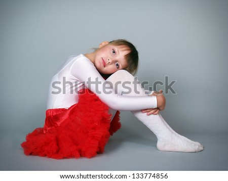 The little beautiful girl the dancer sits in studio - stock photo