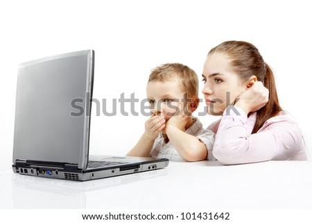 The little boy and beautiful young woman sitting the front of laptop and are very concentrated. A boy is very tired and yawn. - stock photo