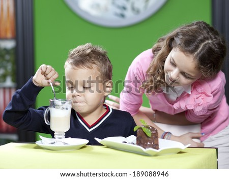 The little boy and his elder sister in cafe have fun - stock photo