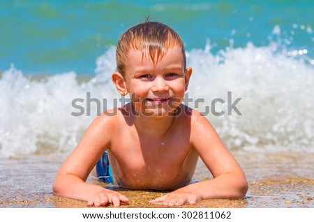 The little boy bathes in the sea with the waves. Big wave in the background. Beach Family composition - stock photo