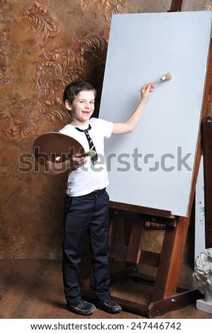 the little boy draws near easel - stock photo