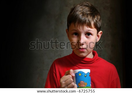The little boy drinking a tea from color cup - stock photo