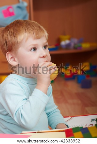 The little boy eats an apple in a children's room - stock photo