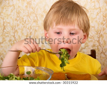 The little boy eats fresh salad - stock photo