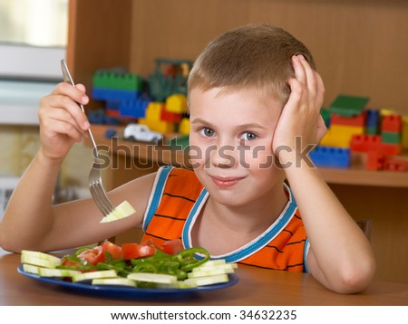 The little boy eats fresh salad on the table