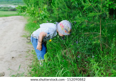the little boy in a cap goes on a grass - stock photo